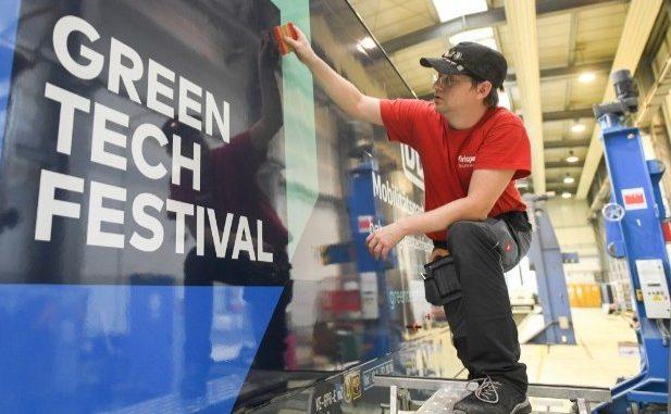 Eine Person klebt einen Greentech-Festival-Werbeaufkleber auf eine Lokomotive der Deutschen Bahn